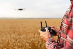 L'agricoltore tiene il regolatore a distanza con le sue mani mentre il quadcopter sta volando sul fondo Il fuco si libra dietro Fotografie Stock Libere da Diritti