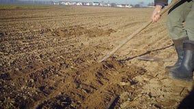 L'agricoltore tratta la terra con una zappa stock footage