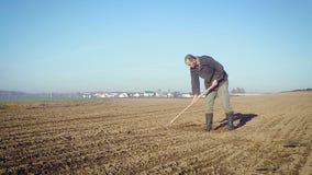 L'agricoltore tratta la terra con una zappa archivi video