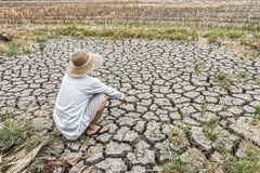 L'agricoltore triste sta sedendosi in un campo agricolo durante la siccità lunga Fotografie Stock Libere da Diritti
