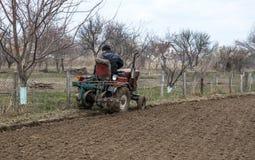 L'agricoltore in un villaggio su un vecchio trattore coltiva un campo Lavoro agricolo della primavera Immagine Stock