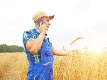 L'agricoltore in una camicia di plaid ha controllato il suo campo Parlando sul pho Fotografia Stock