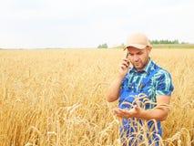 L'agricoltore in una camicia di plaid ha controllato il suo campo Parlando sul pho Fotografia Stock Libera da Diritti