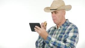 L'agricoltore Use Electronic Tablet mangia e letto i messaggi immagini stock