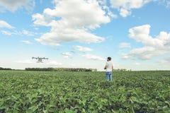 L'agricoltura di controllo di computer di wifi di uso dell'agricoltore del tecnico parla monotonamente il campo verde Fotografia Stock Libera da Diritti