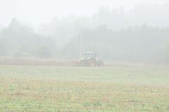 L'agricoltura di mattina del giacimento dell'aratro del trattore funziona la nebbia Fotografia Stock