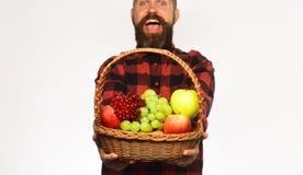 L'agriculteur avec le visage enthousiaste présente des pommes, des raisins et des canneberges photo libre de droits