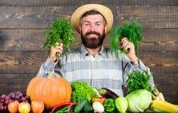 L'agriculteur avec les légumes du cru moissonnent l'excellent homme de récolte de qualité avec la barbe fière de sa récolte en bo photographie stock