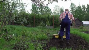 L'agriculteur déchire la terre avec un cultivateur banque de vidéos
