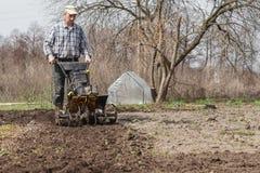 L'agriculteur détache le cultivateur de sol Image libre de droits