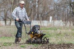 L'agriculteur détache le cultivateur de sol Image stock