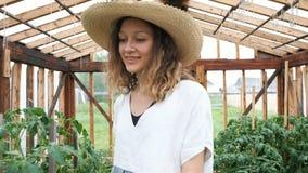 L'agriculteur dans un chapeau de paille et une robe va à la serre chaude, feuilles de reniflement et entourer de danse clips vidéos