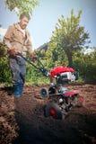 L'agriculteur laboure la terre avec un cultivateur, la préparant pour le planti photos stock