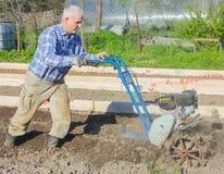 L'agriculteur laboure la terre avec un moteur-bloc Labourage du grou photographie stock libre de droits