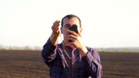 L'agriculteur prélèvent un échantillon du sol fertile noir Poignée d'agriculteur de sol fertile se tenant dans le domaine cultivé banque de vidéos