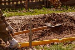 L'agriculteur prépare l'endroit pour la serre chaude utilisant un niveau a photos stock