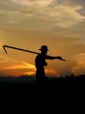 L'agriculteur quand coucher du soleil Photographie stock libre de droits
