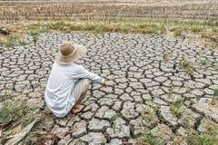 L'agriculteur triste s'assied dans un domaine agricole pendant la longue sécheresse Images stock