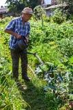 L'agriculteur verse l'eau de la boîte d'arrosage Photographie stock libre de droits
