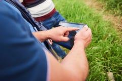 L'agronomo Using una compressa per ha letto un rapporto sul campo dell'agricoltura con lo spazio della copia e sul tono dell'anna Fotografia Stock
