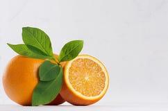 L'agrume avec de demi oranges juteuses et vert laisse le plan rapproché sur la table en bois blanche Image libre de droits