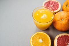 L'agrume coupe en tranches l'orange et le pamplemousse avec du jus sur le backgrou gris Photo libre de droits