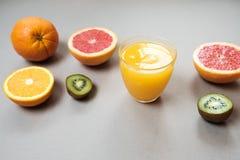 L'agrume coupe en tranches l'orange et le pamplemousse avec du jus sur le backgrou gris Image libre de droits