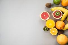 L'agrume coupe en tranches l'orange et le pamplemousse avec du jus sur le backgrou gris Images libres de droits