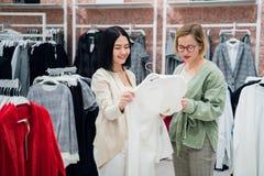 L'aide de consultant en matière de ventes choisit des vêtements pour le client dans le magasin Achat avec le concept de styliste  photo libre de droits