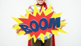 L'aide de sourire de boom d'amusement d'enfant de super héros apprécient le concept Images stock