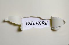 L'aide sociale de mot apparaissant derrière le papier déchiré Photographie stock libre de droits