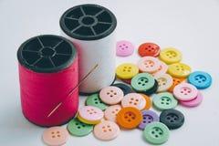 L'aiguille avec la bobine de fil du fil et des boutons, cousent l'instrument Image stock