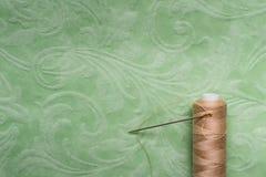 L'aiguille avec une bobine de brun filète sur un fond modelé par vert, l'espace de copie Image stock