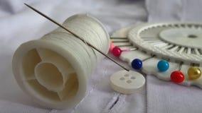 L'aiguille sur la bobine de fil et le ménage blancs de bouton vêtx la réparation Photo stock