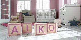 L'aiko de nom écrit avec les cubes en bois en jouet chez la pièce du ` s des enfants photographie stock