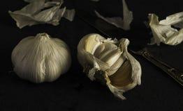 L'ail frais découpe la photo en tranches foncée sur le macro noir de plan rapproché de fond Image libre de droits