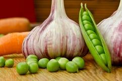 L'ail, les carottes et les pois sont sur la table Image stock
