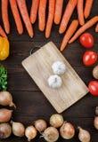 L'ail sur la planche à découper avec des légumes se mélangent sur la table Images stock