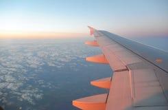 L'aile d'un vol d'avion au-dessus du lever de soleil opacifie Photos stock