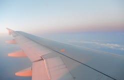 L'aile d'un vol d'avion au-dessus du lever de soleil opacifie Photographie stock libre de droits