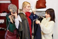 L'aiuto del commesso sceglie i vestiti immagine stock libera da diritti