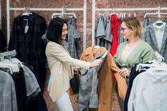 L'aiuto del consulente in materia di vendite sceglie i vestiti per il cliente nel deposito Comperando con il concetto dello stili fotografie stock