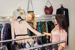 L'aiuto dello stilista sceglie il vestito per il cliente fotografia stock libera da diritti