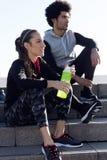 L'ajustement et les jeunes couples sportifs détendant après établissent dans la ville Image libre de droits