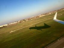 L'ala e l'ombra dell'aeroplano a decollano Fotografia Stock