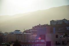 L'alba adorabile luminosa sparge i suoi raggi di sole sopra i mountaines e gli hotel in Tenerife, Spagna Viste marziane Strada de Immagini Stock