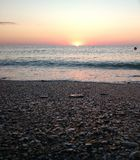 L'alba veduta da una spiaggia si è precipitata dalle onde del mare Immagini Stock
