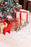 """L'albero del nuovo anno decorato con le sfere e una ghirlanda, regali, l'iscrizione """"nuovo anno """"e una figurina rossa di un caval immagini stock libere da diritti"""