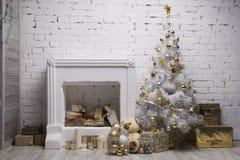 L'albero di natale bianco con le palle dorate e d'argento, i contenitori di regalo, decorazioni di festa ha fornito il camino Immagini Stock