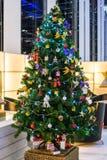 L'albero di Natale con la decorazione variopinta degli ornamenti, prepara nella stanza del partito Immagine Stock